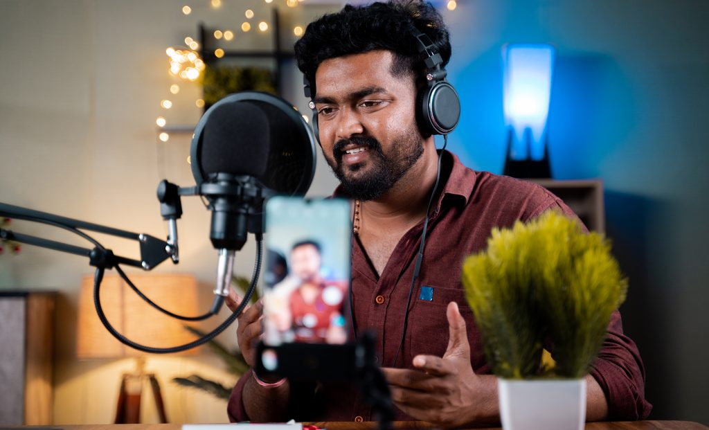 Young social media influencer recording his podcast on mobile phone - concept of vlogging, content creation from home office.
